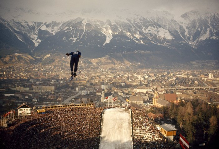 A ski jumper hovers above a packed stadium during the l964 Olympics